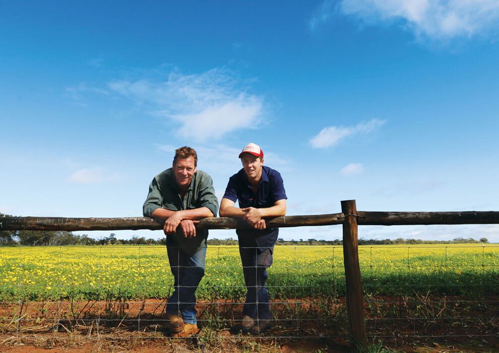 Two farmers leaning on a fence